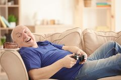 Fat senior man with videogame console and cake lying on sofa at home. Sedentary lifestyle concept Royalty Free Stock Photography