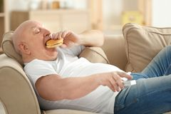 Fat senior man watching TV and eating hamburger while lying on sofa at home. Sedentary lifestyle concept Royalty Free Stock Photos