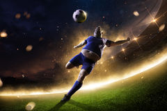 Fat soccer player in action. stadium in fire. Night royalty free stock photography