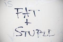 Fat and stupid graffiti. On a door stock photos
