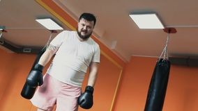 A fat sweat guy in gloves tired after training boxing in Gym. Individual weight loss drills for plump man. Workout with stock footage