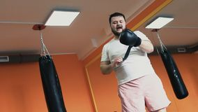 A fat sweat guy tired after training and takes off his boxing gloves in gym. individual weight loss drills for plump man stock video