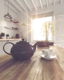 Fat tea pot beside cup with saucer on table Stock Photography