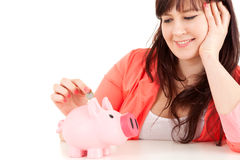 Fat teenage girl putting euro coin in piggy bank Royalty Free Stock Photos