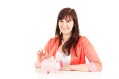 Fat teenage girl putting euro coin in piggy bank Royalty Free Stock Images