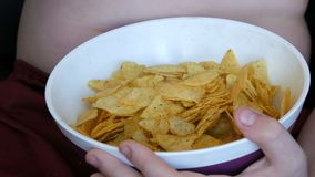 Fat teenager with fat folds on his body is eating potato chips. Unhealthy food, fast food. Children`s nutrition problem. A fat teenager with fat folds on his stock video footage