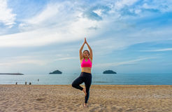 Fat Thai woman poses a standing asana yoga or vriksasana. Lady poses a tree pose on the beach Royalty Free Stock Images