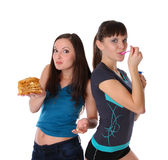 Fat and thin girls eatting Royalty Free Stock Image