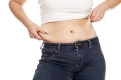 Fat waist. Woman pinching the fat deposits on her waist Stock Image