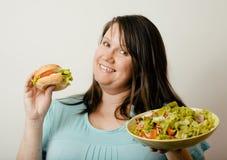 Fat white woman having choice between hamburger Stock Photo