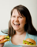 Fat white woman having choice between hamburger and salad Stock Photography