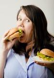 Fat white woman having choice between hamburger and salad Royalty Free Stock Photography