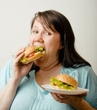 Fat white woman having choice between hamburger and salad Stock Image