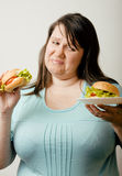 Fat white woman having choice between hamburger and salad Royalty Free Stock Photography