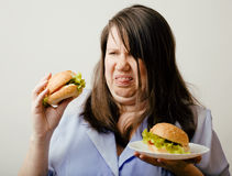 Fat white woman having choice between hamburger and salad Stock Photos