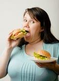 Fat white woman having choice between hamburger Royalty Free Stock Images