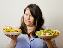 Fat white woman having choice between hamburger and salad close up, unhealth fast food Stock Photography