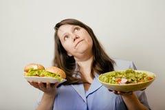 Fat white woman having choice between hamburger and salad close up, unhealth fast food Royalty Free Stock Photography