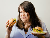 Fat white woman having choice between hamburger and salad close up. Unhealthy food concept Royalty Free Stock Photos