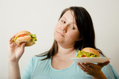 Fat white woman having choice between hamburger and salad close up Stock Photo