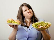 Fat white woman having choice between hamburger and salad close up Royalty Free Stock Images