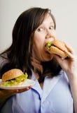 Fat white woman having choice between hamburger and salad close up. Unhealthy food concept Royalty Free Stock Photo