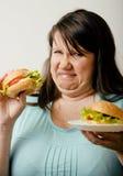 Fat white woman having choice between hamburger and salad close up. Unhealthy food concept Stock Image