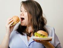 Fat white woman having choice between hamburger and salad close up. Unhealthy food concept Stock Images