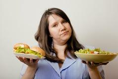 Fat white woman having choice between hamburger and salad close up. Unhealthy food concept Stock Photo