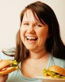 Fat white woman having choice between hamburger Stock Images