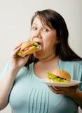 Fat white woman having choice between hamburger Stock Image