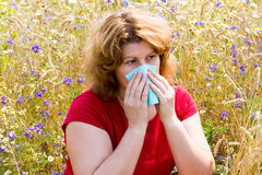 Fat woman with allergic rhinitis in  meadow Stock Images