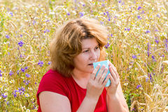 Fat woman with allergic rhinitis in  meadow Royalty Free Stock Image