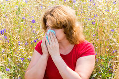 Fat woman with allergic rhinitis in  meadow Royalty Free Stock Photos