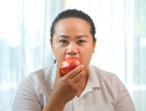 Fat woman with apple Royalty Free Stock Image