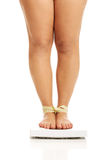 Fat woman checking her weight on a scale Stock Photography