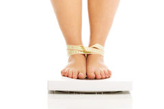 Fat woman checking her weight on a scale Royalty Free Stock Photos