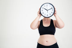 Fat woman covering her face with wall clock Royalty Free Stock Image