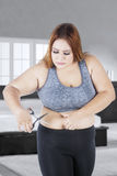 Fat woman cutting her big tummy Stock Photography