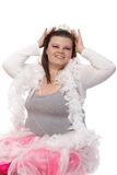 Fat woman daydreaming in tiara smiling. Fat woman daydreaming in tiara and pink tulle skirt, smiling Royalty Free Stock Image
