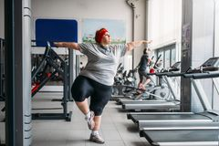 Fat woman doing balance exercise in gym. Calories burning, obese female person on workout in sport club royalty free stock photos