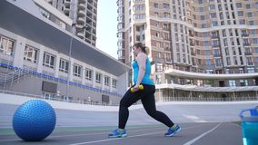 Fat woman doing lunges with dumbbells in stadium. Side view of overweight female working on legs and glutes doing sports exercise lunges with weighting during stock video
