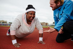 Fat woman doing push ups motivated by personal coach. Push-up challenge during workout on stadium Stock Image
