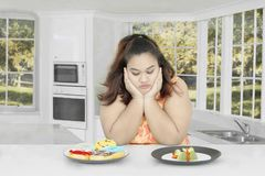 Fat woman doubting to eat Royalty Free Stock Photo