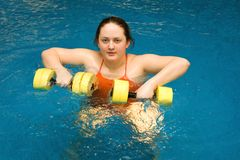 The fat woman with dumbbells in water Royalty Free Stock Image