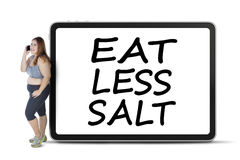Fat woman with eat less salt on board Royalty Free Stock Images