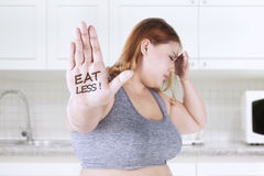 Fat woman with eat less text on hand. Fat woman showing eat les text on her hand while holding her head in the kitchen Stock Photography