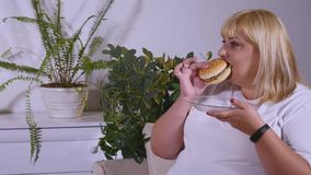 Fat woman eating a burger, watching TV and laughes Royalty Free Stock Photos