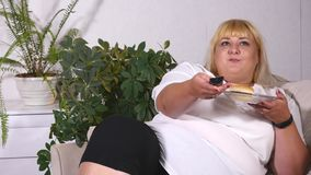 Fat woman eating a burger, watching TV and laughes.  stock image