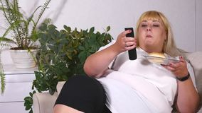 Fat woman eating a burger, watching TV and laughes.  stock images